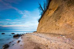 Cliff on sea shore at sunrise. Baltic sea long exposure photo Stock Photos