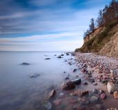 Cliff on sea shore at sunrise. Baltic sea long exposure photo Royalty Free Stock Photo
