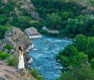 On the cliff stands a beautiful girl in a white dress with dreadlocks. Against the backdrop of fast and turbulent river stock image