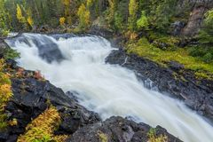 Cliff, stone wall, forest, waterfall and wild river view in autumn. Stock Images