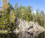 Cliff surrounded by forest near lake Stock Image
