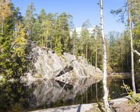 Cliff surrounded by forest near lake Stock Photos