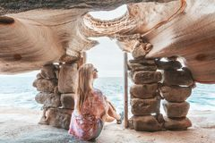 Female sits inside cliff top cave watching the ocean royalty free stock images