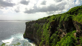 The cliff at Uluwatu Temple, Bali Indonesia. The Uluwatu Temple is perched atop the steep cliff of a limestone peninsula. Breath taking with of the waves coming Royalty Free Stock Images