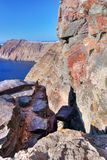 Cliff and volcanic rocks of Santorini island, Greece. View on Caldera. And Aegean sea, sunny day, blue sky Royalty Free Stock Image