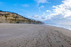 Cliff and wild beach in Sesimbra, close to the Cape Espichel. Po. Foot prints on wild beach and cliff close to the Cape Espichel in Sesimbra, Portugal Stock Photos