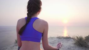 Cliff Yoga with Sea View - calm and peaceful girl meditates in lotus position, concentrates on breathing. 4k stock video footage