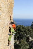 Cliffhanger. Rock climber to climb the wall Stock Image