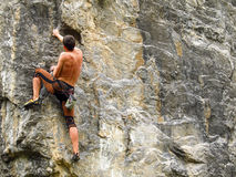 Cliffhanger. Young male climber hanging by a cliff.Cliffhanger Stock Photos
