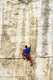 Cliffhanger. Young male climber hanging by a cliff Royalty Free Stock Photography