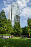 Clifford Chance Offices and Jubilee Park, Docklands. LONDON, UK - JULY 1, 2014:  Sunbathers enjoying the greenery of Jubilee Park in London's Docklands Royalty Free Stock Photos