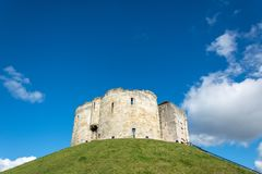 Clifford`s Tower on grass covered hill with blue sky Royalty Free Stock Image
