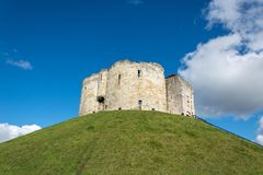 Clifford`s Tower on grass covered hill with blue sky Royalty Free Stock Photo