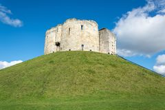 Clifford`s Tower on grass covered hill with blue sky Stock Photography