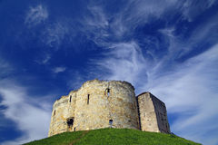 Clifford's Tower in York UK. Clifford's Tower at York, UK on a sunny day with blue sky and copyspace Royalty Free Stock Image