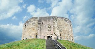 Clifford`s Tower in York, Yorkshire, UK. In a beautiful blue sky