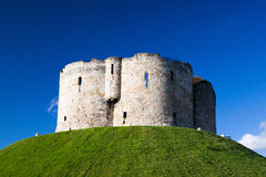 The cliffords tower. Medieval landmark architecture of cliffords tower in the centre of the historic city of york england under a clear blue sky Royalty Free Stock Photography