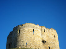 Cliffords tower in York, England. Cliffords tower under a sunny blue sky in York, England Royalty Free Stock Photography