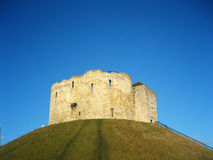 Cliffords tower in York, England. Cliffords tower under a sunny blue sky in York, England Stock Photo