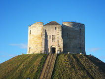 Cliffords tower in York, England. Cliffords tower under a sunny blue sky in York, England Royalty Free Stock Images