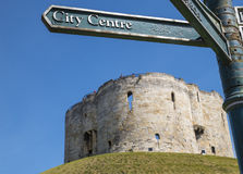 Cliffords Tower in York. A signpost pointing towards the city centre with Cliffords Tower in the background, in the historic city of York, England Stock Image