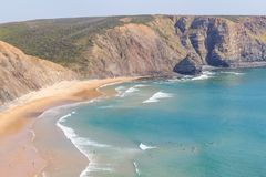 Cliffs, beach and waves in Arrifana Royalty Free Stock Photos
