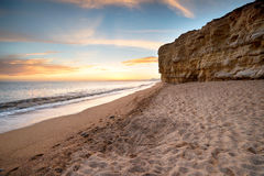 Cliffs at Burton Bradstock in Dorset. Sunset over the cliffs at Hive Beach at Burton Bradstock near Bridport on the Dorset coast Stock Photography