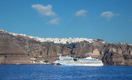 The cliffs of calera with the cruise and Fira town in the background. Stock Image