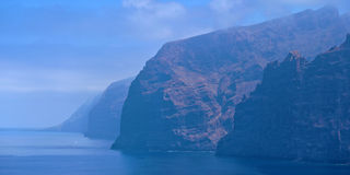 Cliffs of the Giants at Tenerife in morning fog. Cliffs of the Giants, or Acantilados de Los Gigantes, vertical cliffs along the western coast of Tenerife island Royalty Free Stock Photography