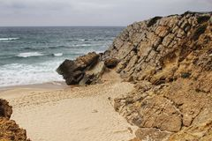 Cliffs at Guincho beach under cloudy sky in Portugal royalty free stock image