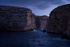 Cliffs in Island of Gozo at dusk. Winter, Malta. Cliffs in Island of Gozo Dwejra Bay at dusk. On right side Fungus Rock. Winter, Malta Stock Photography
