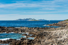 Cliffs, islands and boat in the Rias Baixas, Galicia Royalty Free Stock Images