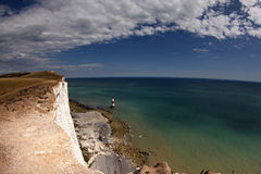 Cliffs And Lighthouse At Beachy Head. Wide view of the sea and sky off the cliffs at Beachy Head, East Sussex, UK. The lighthouse is visible in the distance stock photos