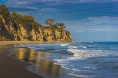 Cliffs of Malibu. Beachside view of beautiful blue Pacific Ocean and stunning cliffs surrounding Dume Cove on a sunny day with clouds in the sky, Point Dume Stock Photo