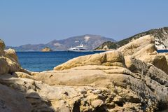 Cliffs of the Marathias beach, Greece. Yacht in the sea against the background of the royalty free stock photos