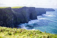 Cliffs of Moher at Alantic Ocean in Western Ireland with waves battering against the rocks. Cliffs of Moher, Alantic Ocean in Western Ireland with waves royalty free stock image