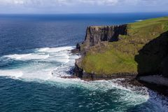 Cliffs of Moher at Alantic Ocean in Western Ireland with waves battering against the rocks. Cliffs of Moher, Alantic Ocean in Western Ireland with waves stock images