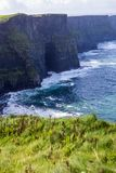 Cliffs of Moher at Alantic Ocean in Western Ireland with waves battering against the rocks. Cliffs of Moher, Alantic Ocean in Western Ireland with waves stock photo