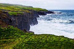 Cliffs of Moher panorama at the Alantic Ocean in Western Ireland with waves battering against the rocks. Cliffs of Moher panorama at the Alantic Ocean in Western royalty free stock photo