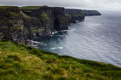 Cliffs of Moher rise clearly out of the Atlantic Ocean Royalty Free Stock Photography