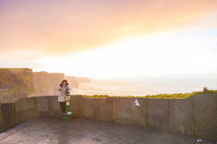 Cliffs of Moher at sunset in Co. Clare Ireland Europe. Woman tourist on cliffs of Moher at sunset in Co. Clare Ireland Europe. Beautiful landscape nature Stock Image