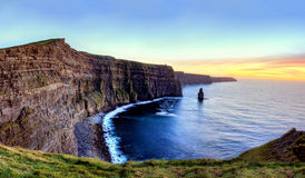 Cliffs of Moher at sunset in Ireland. Panoramic view of Cliffs of Moher at sunset in Ireland Stock Images