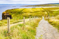 Cliffs of Moher trail with Doolin village and farm fields in background. Clare, Ireland royalty free stock image