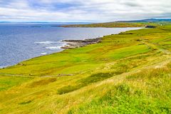 Cliffs of Moher trail with Doolin village and farm fields in background. Clare, Ireland royalty free stock photography