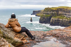 Cliffs of Moher. Young tourist woman admire the view at Cliffs of Moher Royalty Free Stock Photography
