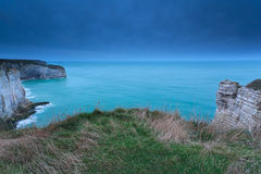 Cliffs in ocean in dusk Stock Photos
