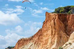 Cliffs and paragliders at the Praia de Falésia at Albufeira in Portugal stock photography