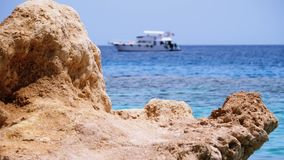 Cliffs and pleasure boats in the red sea on the Beach of Egypt. Rocky Beach on Red Sea near the Coral Reef. View of the Sharm El Sheikh coastline. Stone Beach stock video