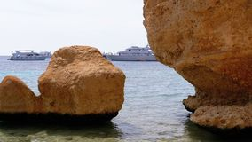 Cliffs and pleasure boats in the red sea on the beach of Egypt. Rocky Beach on Red Sea near the Coral Reef. View of the Sharm El Sheikh coastline. Stone Beach stock video footage