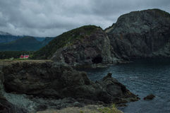 Cliffs and Red House along a Rugged Coastline at Lark Harbor in Newfoundland Royalty Free Stock Photo